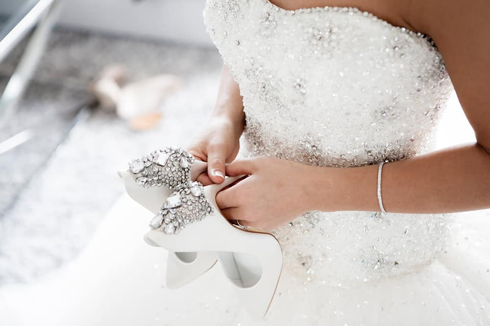 bride holding her white shoes, one of her wedding accessories