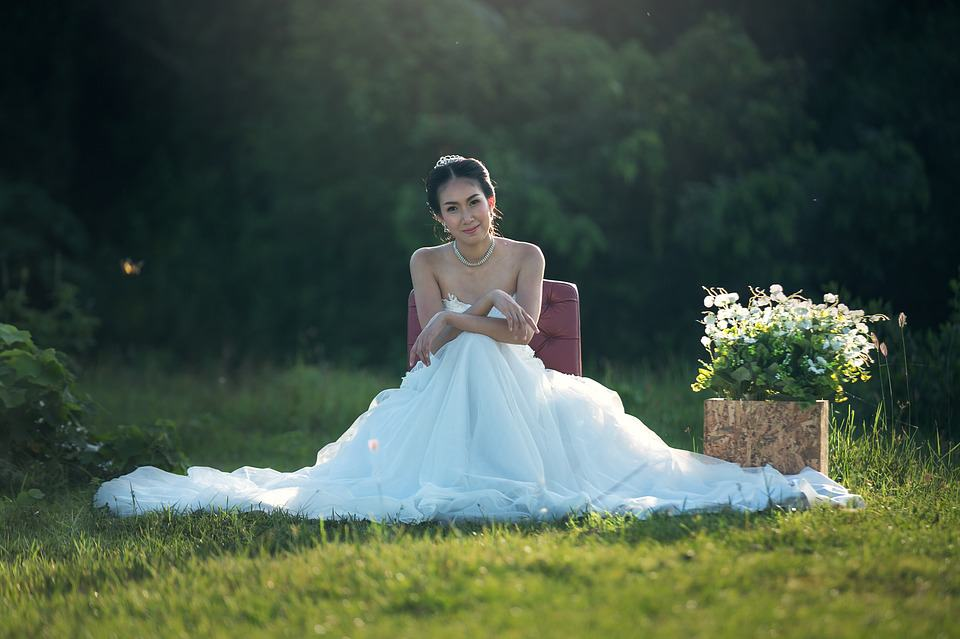 bride sitting in the grass