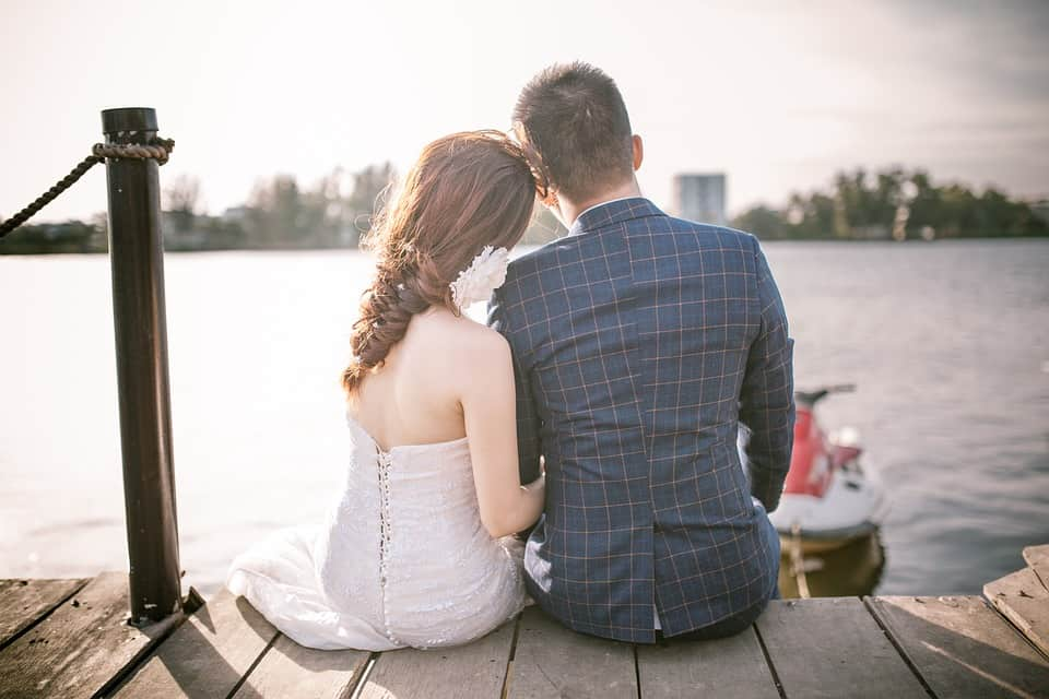 wedding couple sitting by the lake