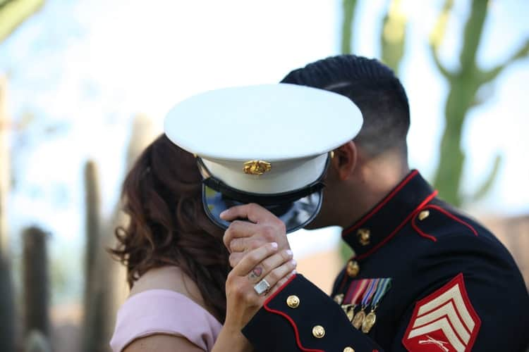 man and woman kissing behind a marine cap