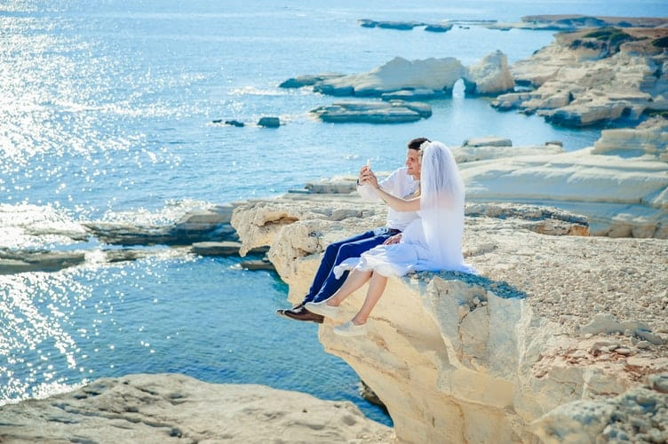 bride and groom sitting over a cliff