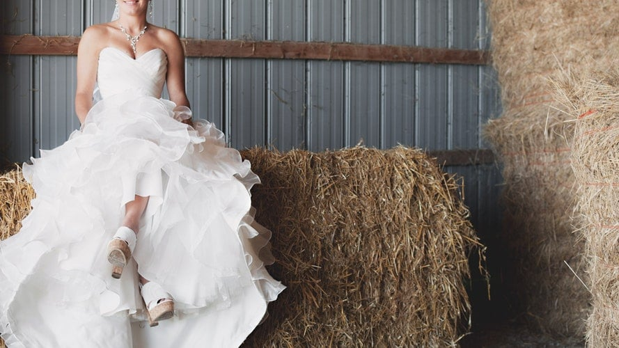 woman in wedding dress sitting in a barn