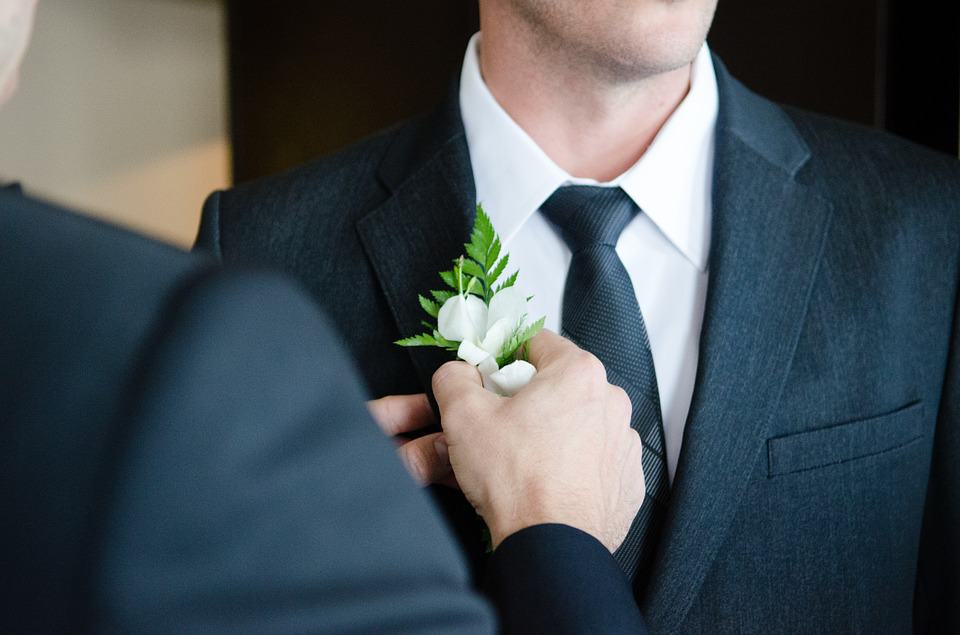man putting corsage on a man wearing black suit