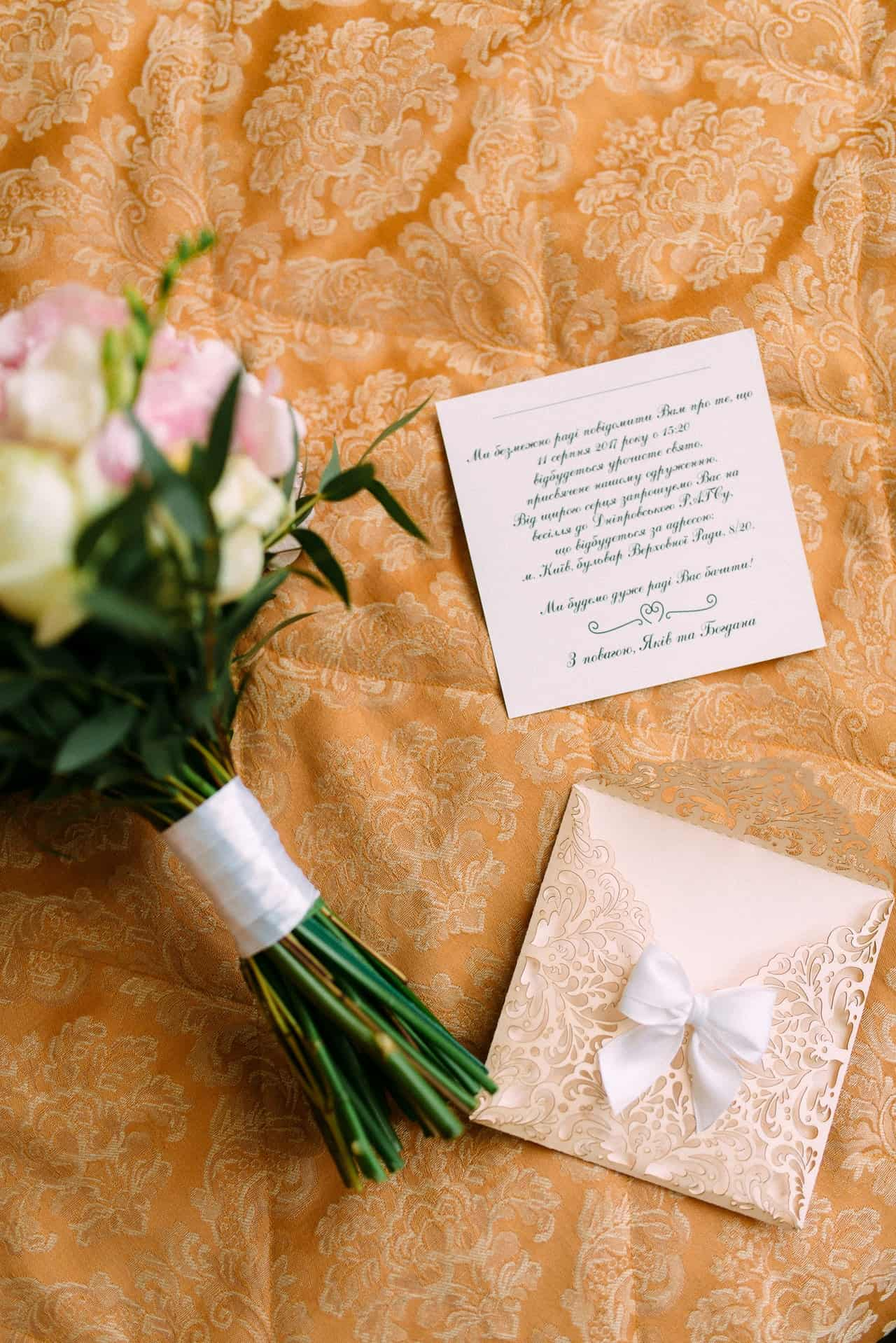 wedding invitation card and letter beside a bouquet of flowers
