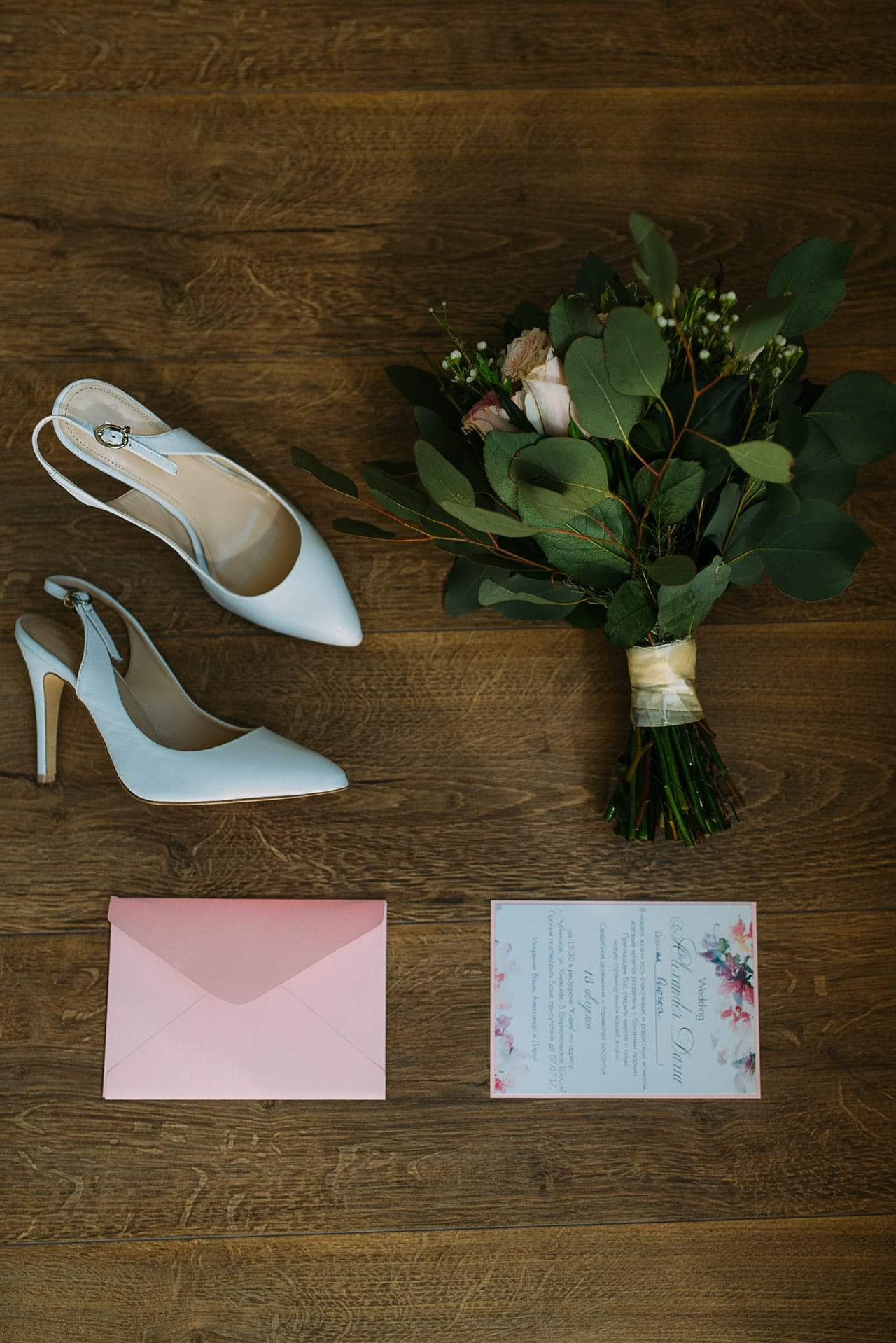 wedding invitation behind pair of bridal shoes and bouquet of flowers