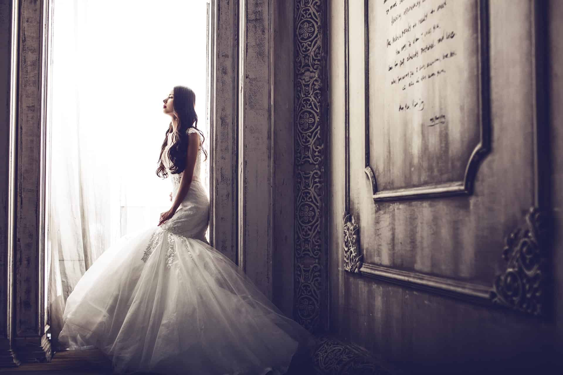 woman in a wedding dress sitting by the window