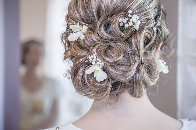 a bride with trendy bridal bun fixed by her hairstylist, one of the wedding