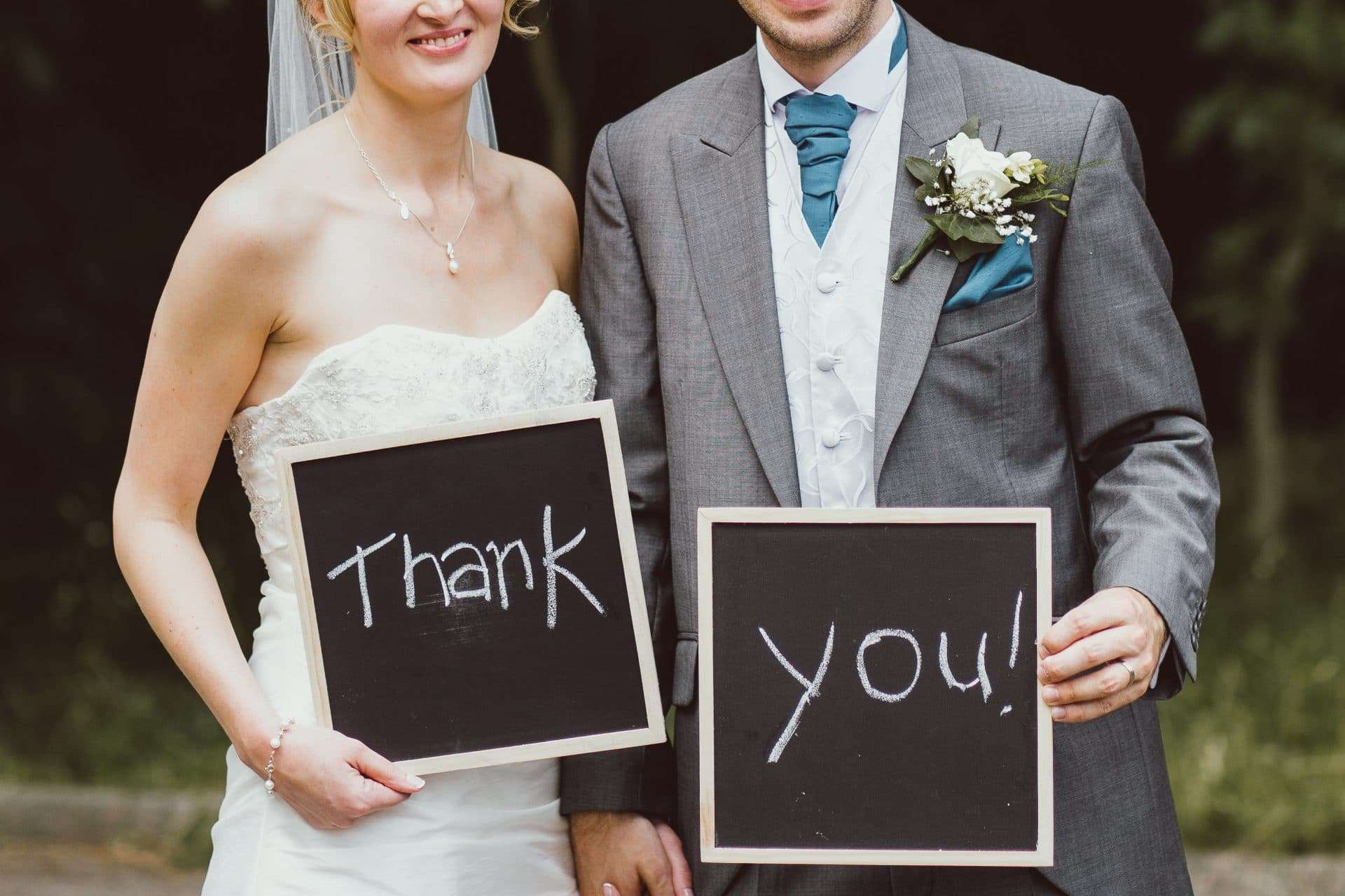 bride and groom holding chalk boards in which the words thank you! are written
