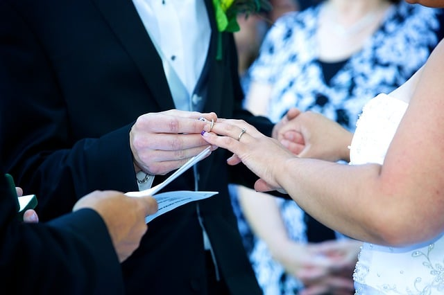 groom and bride exchanging vows and rings in front of a wedding officiant