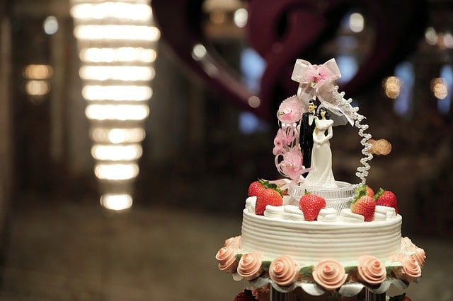a perfect wedding cake with couple figurine and fresh strawberries