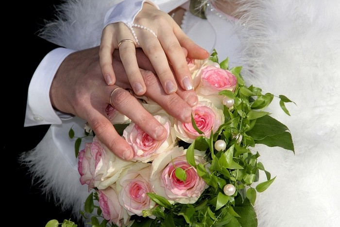 groom and bride's hands on top of the flowers show their wedding rings