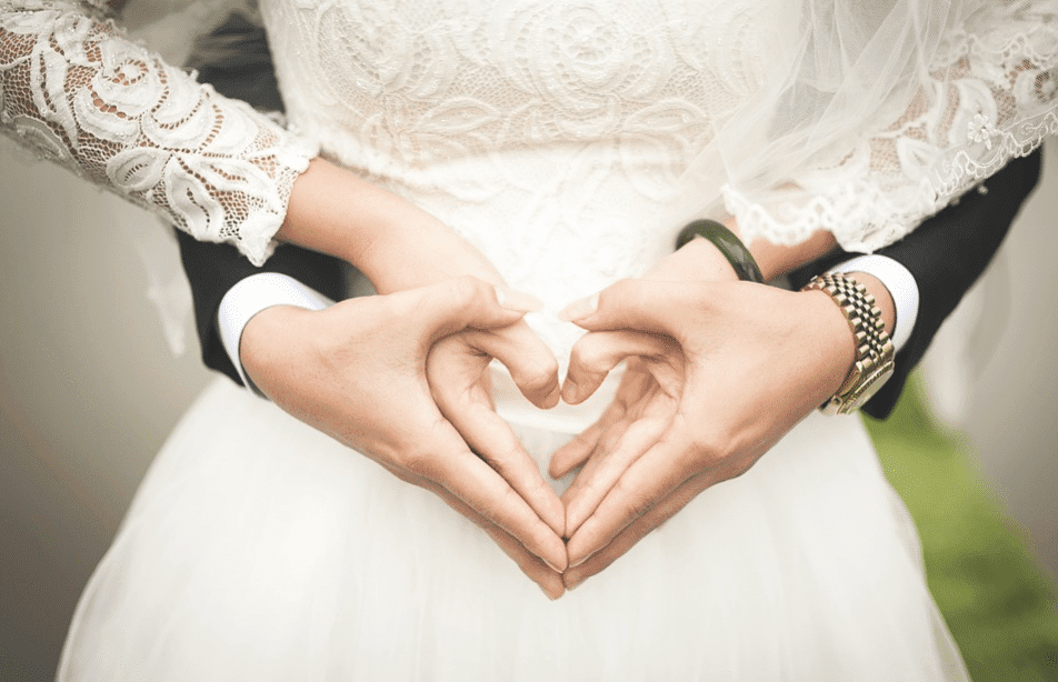 bride and groom on a heart shape hands