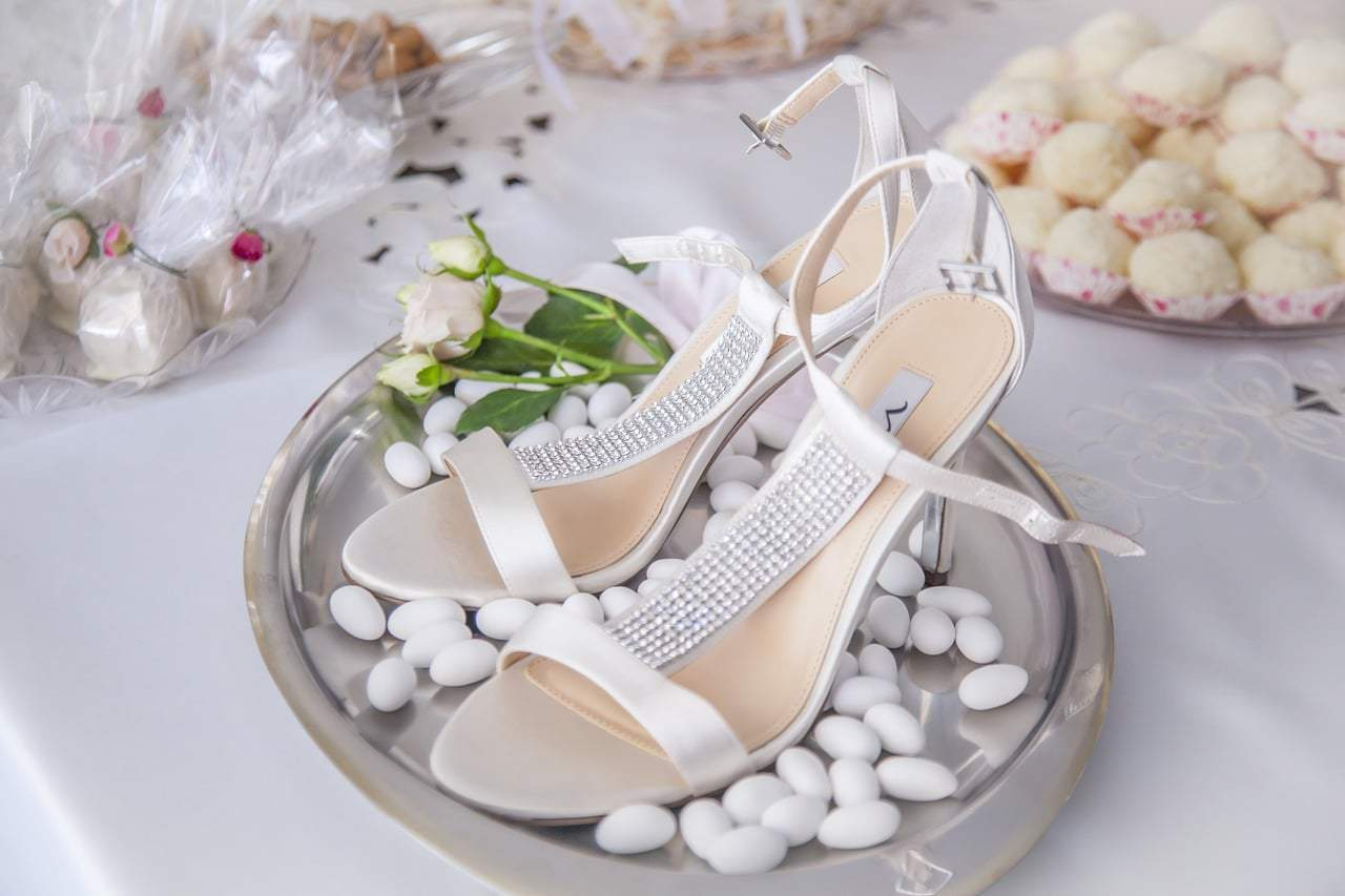 shoe bride surrounded withh sugared almonds with flower